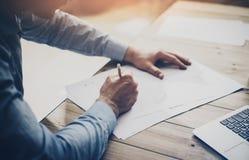Processo de trabalho Homem de negócios que trabalha na tabela de madeira com projeto novo Caderno genérico do projeto na tabela h fotografia de stock