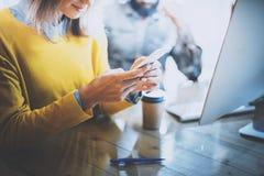 Processo de trabalho no escritório moderno Mulher de sorriso que olha a seus telefone celular e mensagem de datilografia na tabel Fotografia de Stock