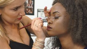 Processo del primo piano di applicazione del trucco per il modello afroamericano splendido in un salone stock footage