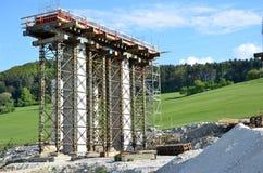 Processo della costruzione delle colonne, che stanno andando essere una parte di nuova strada principale Immagine Stock