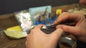 Processo delle gemme delle inserzioni in un anello d'argento facendo uso delle pinzette dal gioielliere video d archivio