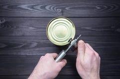 Processo di apertura del barattolo di latta su un fondo di legno scuro immagini stock