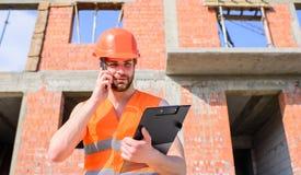 Processo di controllo di telefonata dell'ingegnere Supporto protettivo del casco del tipo davanti a costruzione fatta dai mattoni immagine stock libera da diritti