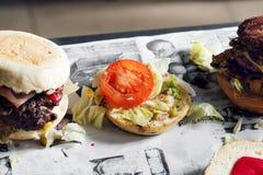 Processo di cottura dell'hamburger cuoco unico sul tavolo da cucina che distingue gli ingredienti dell'hamburger Manzo Patty cuci Immagini Stock Libere da Diritti