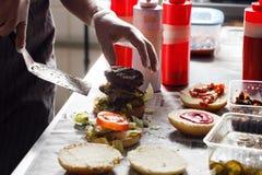 Processo di cottura dell'hamburger cuoco unico sul tavolo da cucina che distingue gli ingredienti dell'hamburger Manzo Patty cuci Fotografia Stock Libera da Diritti