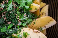 Processo di cottura delle patate al forno Fragrante inzuppato in spezie e salsa, patate fresche con buccia La patata è pronta a a immagine stock