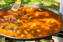 Processo di cottura paella o del jambalaya spagnola in grande padella piana Metallo Turner che lancia gli ingredienti in salsa al Fotografia Stock