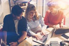 Processo di Coworking all'ufficio soleggiato Gruppo di affari che si siede alla sala riunioni e che per mezzo dei dispositivi mob fotografia stock libera da diritti