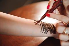 Processo di disegno dell'ornamento di menhdi del hennè sulla mano della donna immagini stock libere da diritti