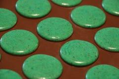 Processo di fabbricazione dei macarons Macarons verdi sullo strato di cottura del silicone Fotografia Stock