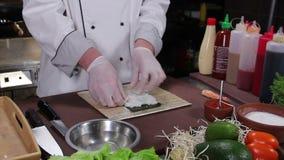 Processo di fabbricazione dei rotoli di sushi, riso di diffusione del cuoco sopra il nori stock footage