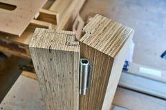 Processo di fabbricazione del legno della porta Installazione della cerniera di porta Fabbricazione della mobilia fotografie stock