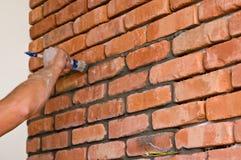 Processo di fabbricazione del muro di mattoni rosso, rinnovamento domestico immagine stock