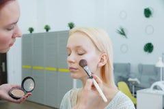 Processo di fabbricazione del trucco Truccatore che lavora con la spazzola sul fronte di modello fotografia stock
