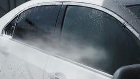 Processo di lavaggio dell'automobile Il detersivo di schiumatura copre la macchina, la libera dalla sporcizia Movimento lento stock footage