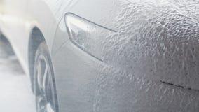 Processo di lavaggio dell'automobile La schiuma dello spruzzo copre la macchina e la libera dalla sporcizia Movimento lento archivi video