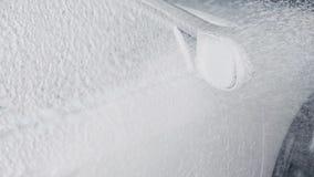 Processo di lavaggio dell'automobile La schiuma dello spruzzo copre la macchina e la libera dalla sporcizia Movimento lento video d archivio