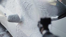Processo di lavaggio dell'automobile su self service, detersivo di schiumatura con il lavaggio di alta pressione fuori da sporciz video d archivio