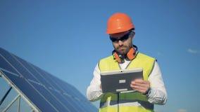 Processo di lavoro di un ispettore maschio che sta con un computer vicino il pannello solare video d archivio