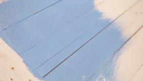Processo di pittura del bordo di legno: un artista applica il colore blu con una spazzola archivi video