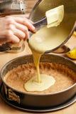 Processo di produrre una torta di formaggio deliziosa del limone - pasta di versamento fotografia stock libera da diritti
