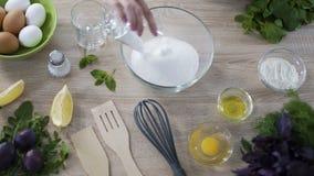 Processo di trasformare i pancake, farina di versamento della ragazza, aggiungendo zucchero e sale la ciotola video d archivio
