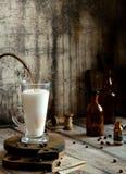Processo di versamento del caffè in latte spumoso sui supporti di vetro del latte sui bordi di legno sulla tavola rustica grigia fotografie stock libere da diritti