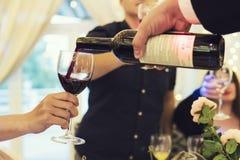 Processo di versamento del vino rosso nei vetri sopra la tavola festiva L'uomo riempie i vetri di alcool per bere i pani tostati  immagini stock