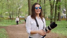 Processo do funcionamento do fotógrafo da jovem mulher que dispara fora na natureza do parque video estoque