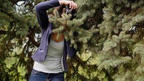 Processo do funcionamento do fotógrafo da jovem mulher que dispara fora na natureza do parque vídeos de arquivo