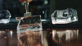 Processo do movimento lento de gelo que racha-se no fundo do contador da barra filme