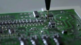 Processo mec?nico da cria??o de circuitos eletr?nicos Criando uma placa eletrônica A agulha do metal ajusta as microplaquetas na vídeos de arquivo