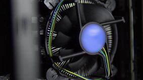 The processor cooler on the motherboard is spinning closeup. CPU cooling system on pc. View of the computer from the