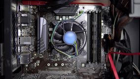 The processor cooler on the motherboard is spinning. CPU cooling system on pc. View of the computer from the inside.
