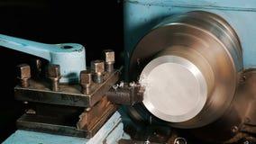 Processos do trabalhador um boleto de alumínio em um torno feche acima no movimento lento filme