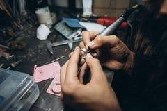 Processos mestres da menina a placa de metal na oficina home foto de stock