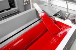 Processred ink in offset print machine fountains Stock Photo
