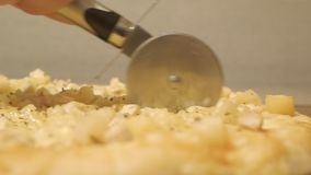 Processus, étapes de faire cuire la pizza la pizza juteuse et appétissante est coupée avec un coupeur de pizza en métal sur le fo clips vidéos