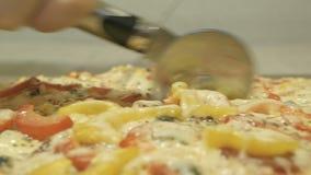 Processus, étapes de faire cuire la pizza la pizza juteuse et appétissante est coupée avec un coupeur de pizza en métal sur le fo banque de vidéos