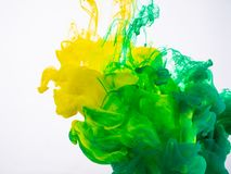 Processus d'encre acrylique se mélangeant sous la fin de l'eau  Peinture jaune et verte se dissolvant dans l'eau, fond abstrait photo libre de droits