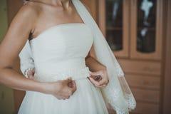 Processus d'habillement d'une robe de mariage Photographie stock libre de droits