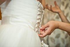 Processus d'habillement sur une robe de mariage Photographie stock libre de droits
