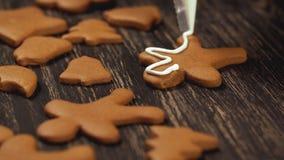 Processus de décoration des biscuits de Noël Fin vers le haut de garnir des bonhommes en pain d'épice banque de vidéos