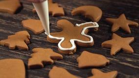 Processus de décoration des biscuits de Noël Fin vers le haut de garnir des bonhommes en pain d'épice clips vidéos