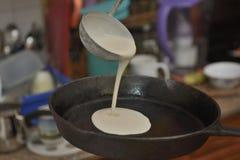 Processus de la cuisson de la crêpe sur une fin de poêle de fonte brute  images stock