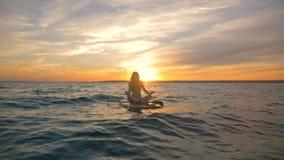 Processus de méditation sur une planche de surf Le surfer féminin médite sur son conseil tout en flottant sur l'eau banque de vidéos