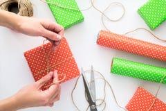 Processus de paquet et d'envelopper le boîte-cadeau de Noël et de nouvelle année avec des mains de femme Papier d'emballage, cise Image stock
