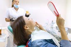 Processus de traitement dentaire Patient f?minin regardant ses dents dans le miroir tout en se reposant dans la chaise dentaire photos libres de droits
