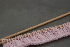 Processus de tricotage fait main Laine de tricotage de bobine rose de fil et aiguilles en bois au-dessus de Gray Background Copie Images stock