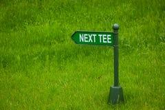 Prochain champ de golf de direction de flèche de signe de pièce en t Photographie stock